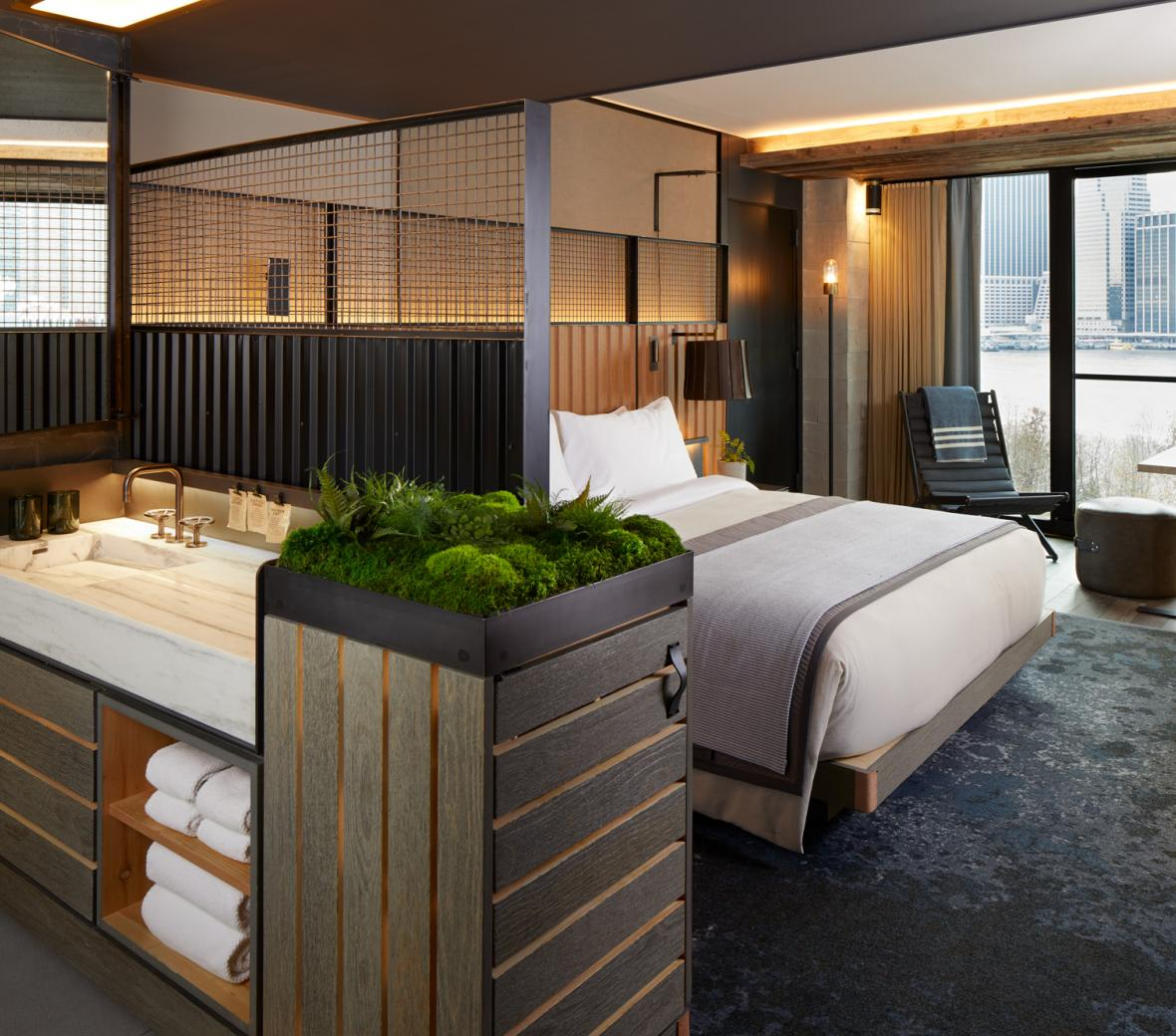 A king sized bed in a suite with a view of the Manhattan skyline