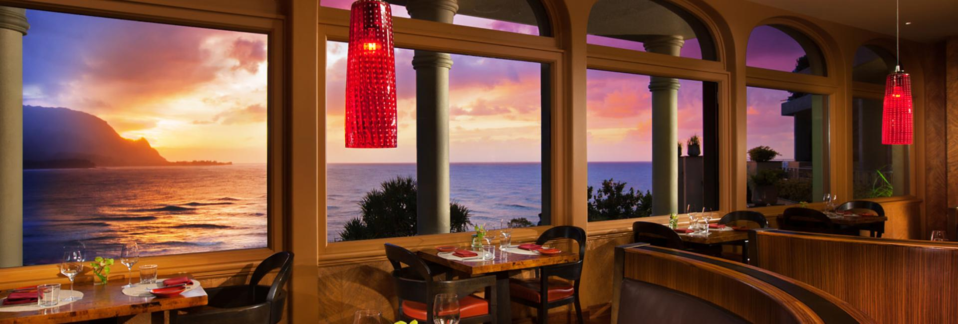 Tables set in the dining area of the Kauai Grill overlooking the ocean