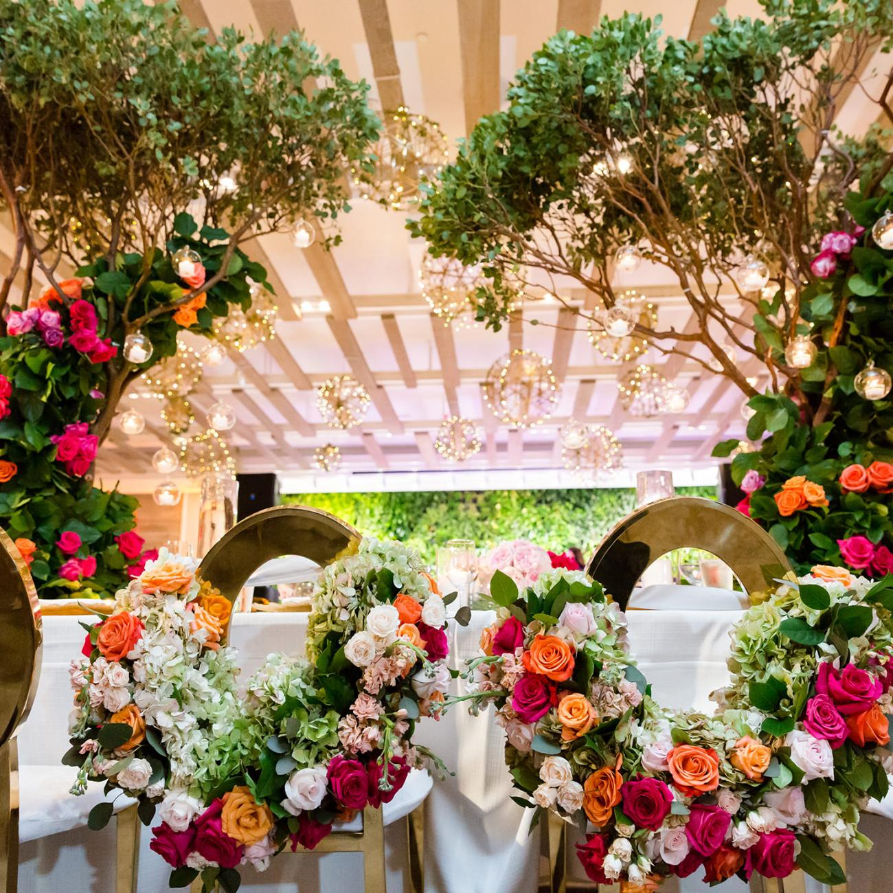 The head table of a wedding reception decorated with colorful flowers