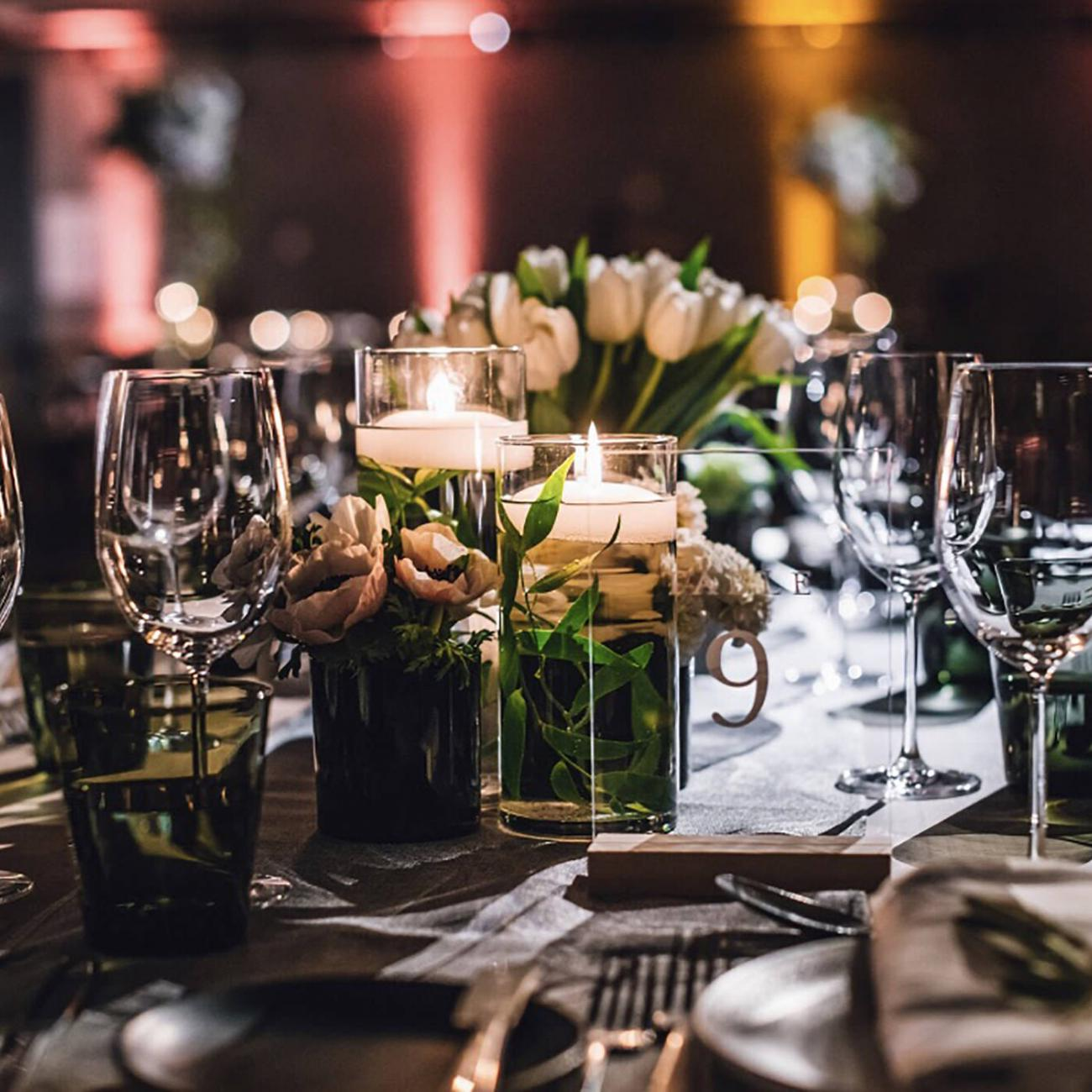 A table set with glassware, flowers and candles
